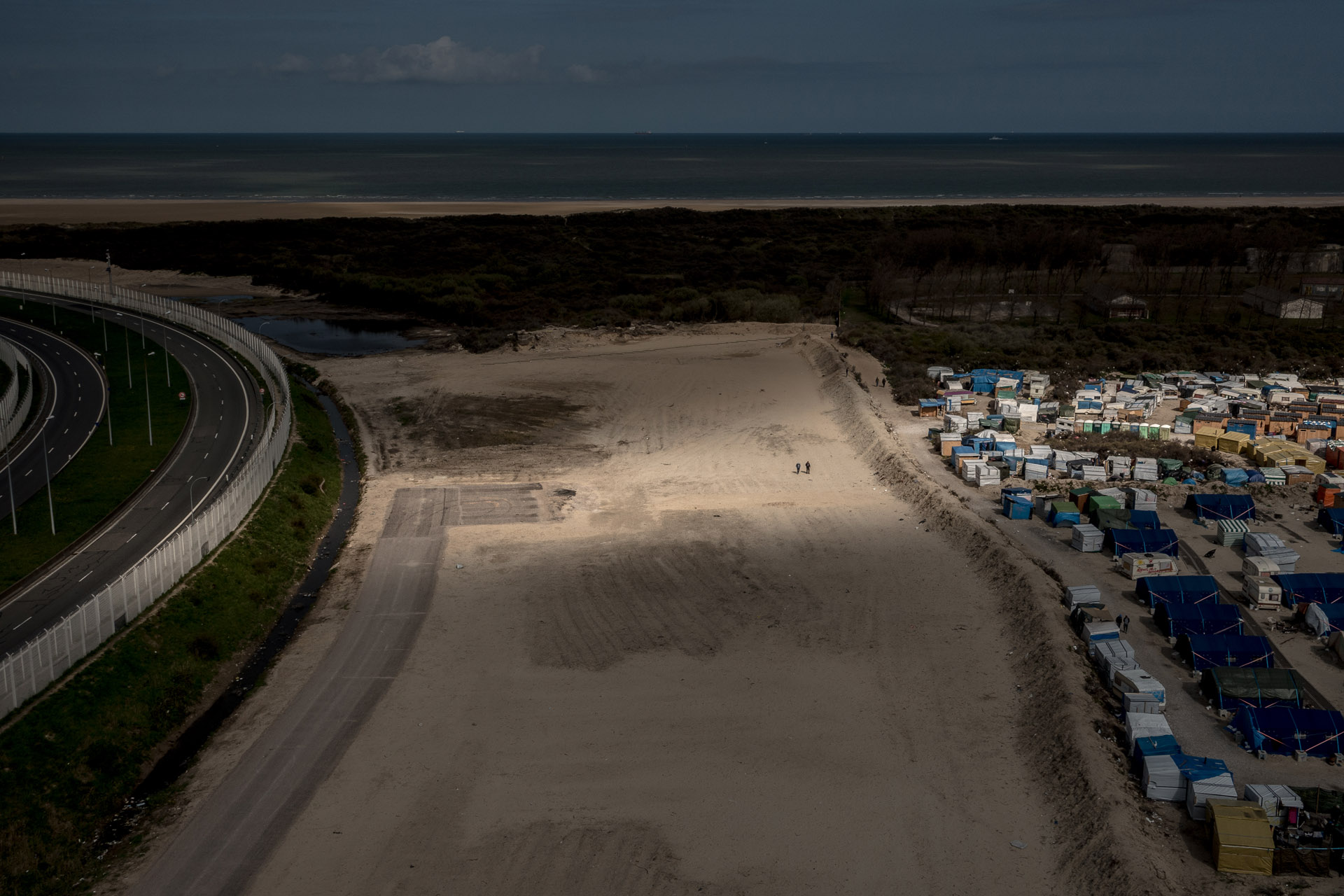 Migrants walk in the bufferzone in Calais.